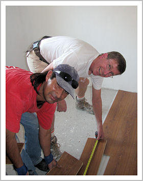Volunteers hard at work laying floors in the new bedroom.