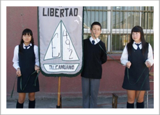 Three Students from Escuela Libertad standing beside their school flag during the inauguration ceremonies