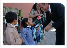 Sr. Ramiro Trucco, Canada's Honorary Consul in Concepción, handing a new backpack filled with school supplies to a young female student at Escuela Libertad