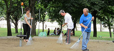 A team from different sections of the embassy is cleans the sandbox of the playground
