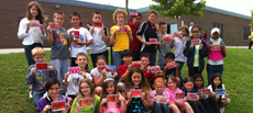Canadian fourth graders pose with their Dream Time style artwork in front of their school.