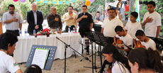 Ambassador Pierre Giroux and local leaders listen to youth band play Salvadorian national Anthem