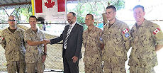 Members of the Canadian Force and Canadian Ambassador to South Sudan Nicholas Coghlan shake hands in the inauguration ceremony.