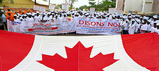 Advocates against CEFM march with a large Canada flag.