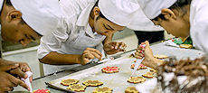 Bake Masters glazing Canadian maple leaf cookies.