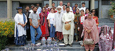 Canadian High Commission staff, organizers and artists pose in front of traditional Pakistani pottery.