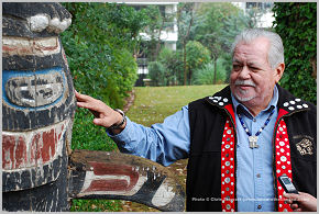Chief Tony Hunt standing next to the totem pole.