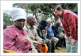 Canadian High Commissioner, David Collins speaks to a member of the local community in Kawangware