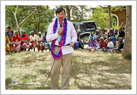 High Commissioner Collins speaks into a microphone, wearing colourful garments.