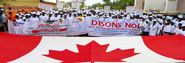 Des militants luttant contre les MEPF marchent sous un grand drapeau du Canada.