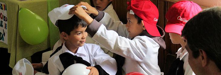 Les élèves de l'école « canadienne » jouent avec leurs ballons rouges et blancs et leurs chapeaux canadiens